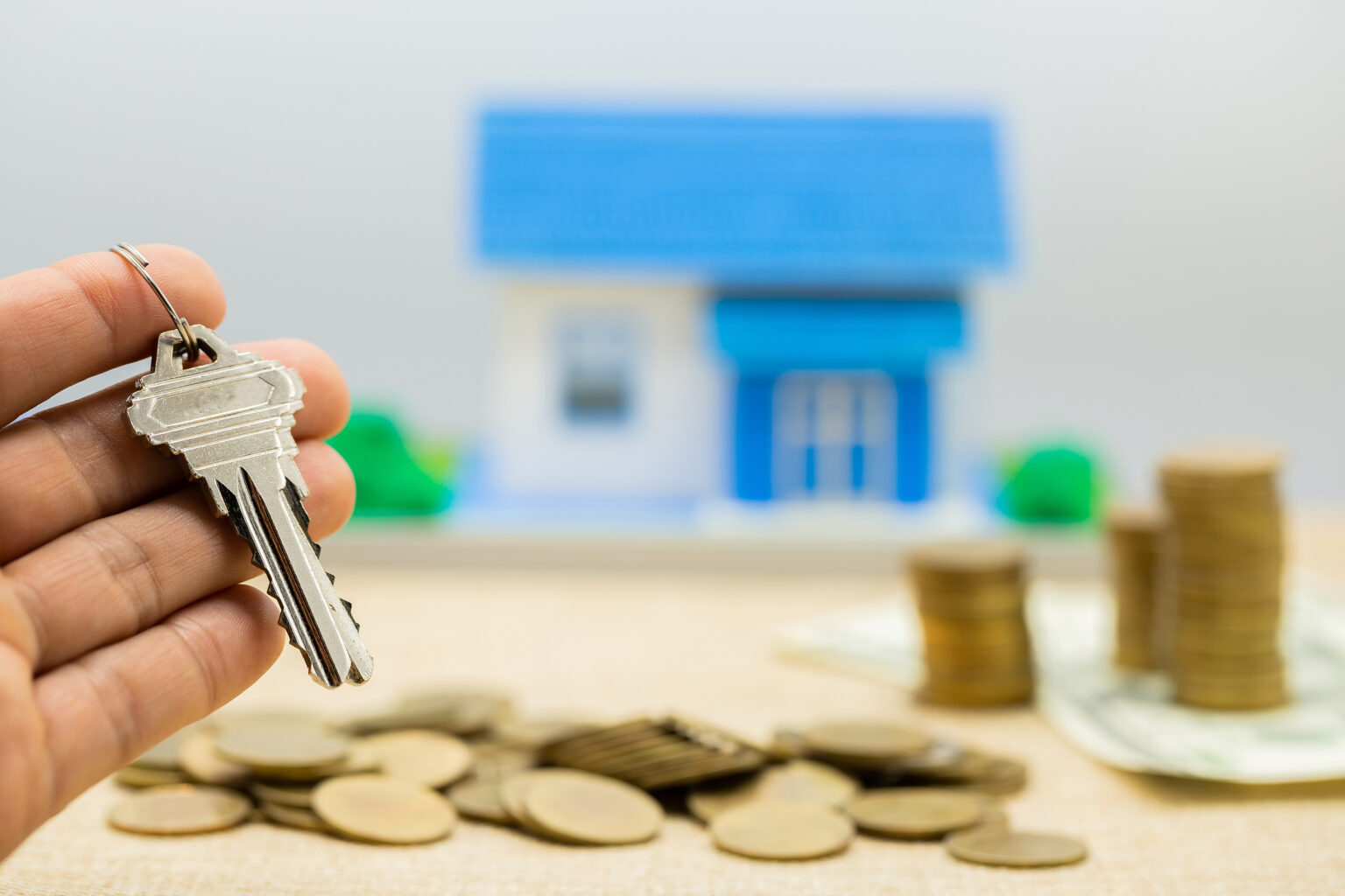 Keys and money piles and houses for mortgage loan concepts.